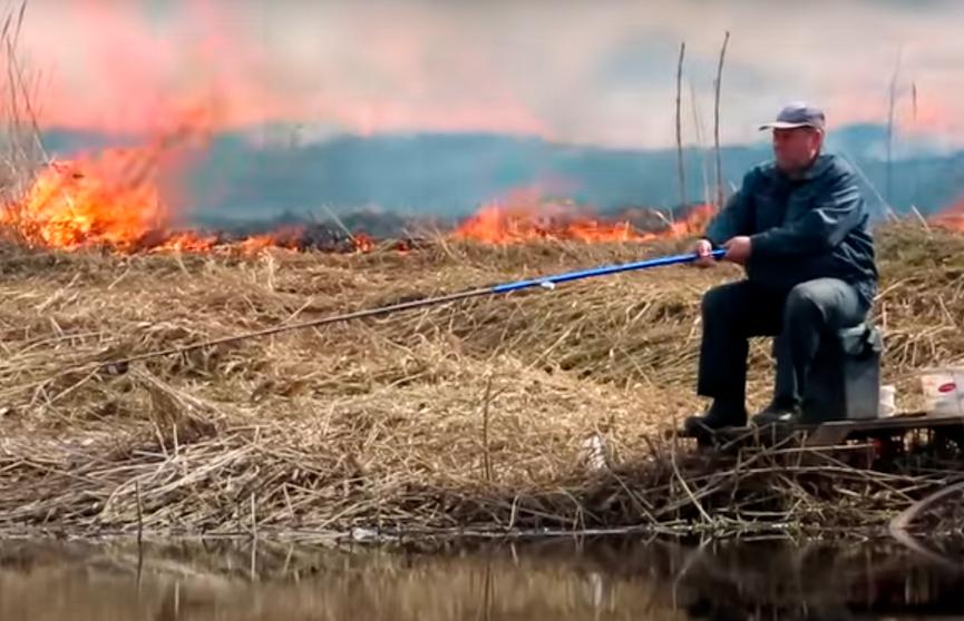 И пусть весь мир подождет! Белорус с невозмутимым видом продолжил рыбачить на фоне пожара и стал мемом