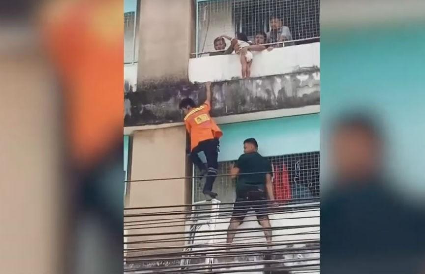 Неравнодушные прохожие сняли с карниза здания в Бангкоке маленькую девочку (ВИДЕО)