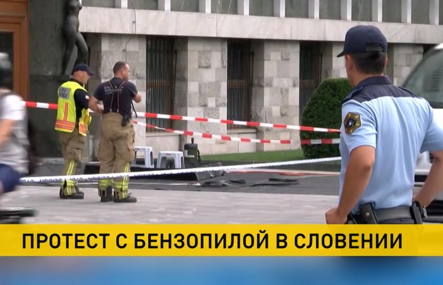 Мужчина с бензопилой пришел на антиковидный протест к зданию парламента в Словении