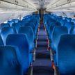 Стюардесса ногами закрыла верхние багажные полки в самолете